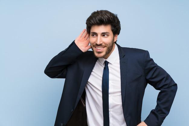 Homem negócios, sobre, isolado, parede azul, escutar, algo, pondo mão, ligado, a, orelha Foto Premium