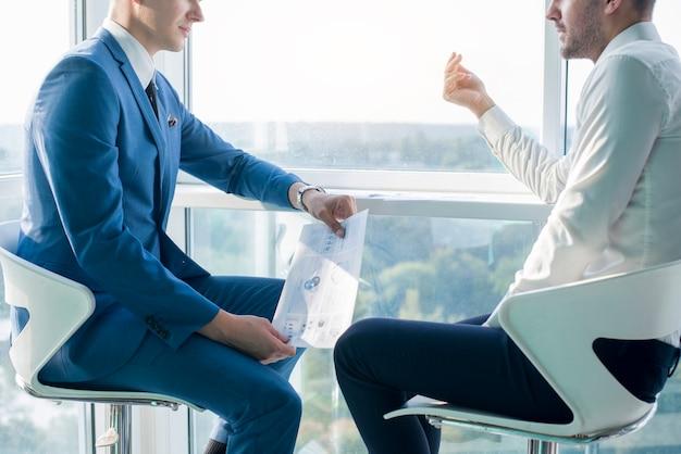 Homem negócios, tendo, conversa, com, seu, colega masculino, segurando, infographic, folha Foto Premium