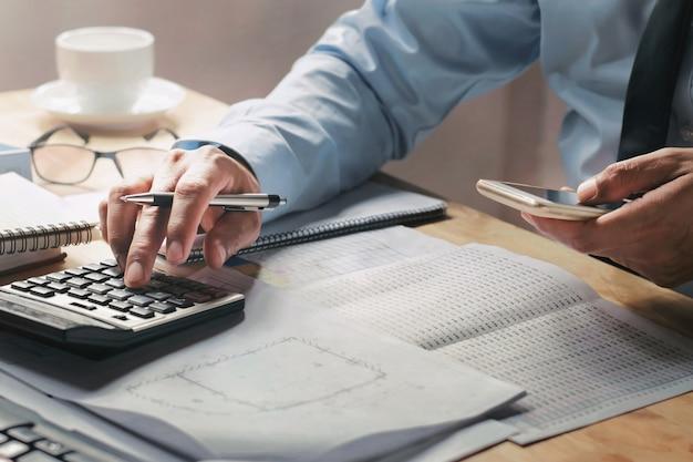 Homem negócios, trabalhar, escrivaninha, em, escritório, usando, calculadora, e, móvel Foto Premium