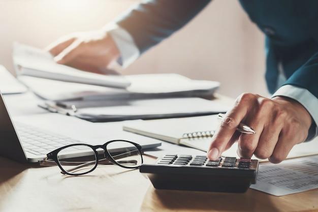 Homem negócios, usando, calculadora, para, calcule, trabalhando, em, escritório Foto Premium