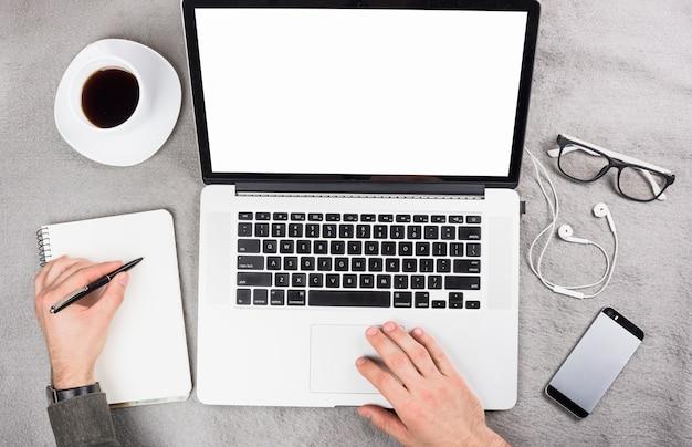 Homem negócios, usando, tablete digital, escrita, ligado clipboard, com, caneta, sobre, a, cinzento, escrivaninha Foto gratuita