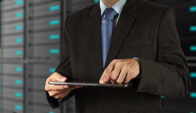 Homem negócios, usando, tabuleta, computador, e, servidor, sala, fundo Foto Premium