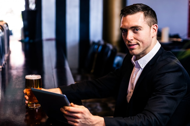 Homem negócios, usando, tabuleta, tendo, um, cerveja, um bar Foto Premium