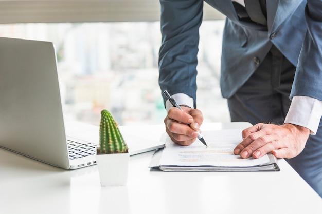 Homem negócios, verificar, documento, com, caneta, escrivaninha Foto gratuita
