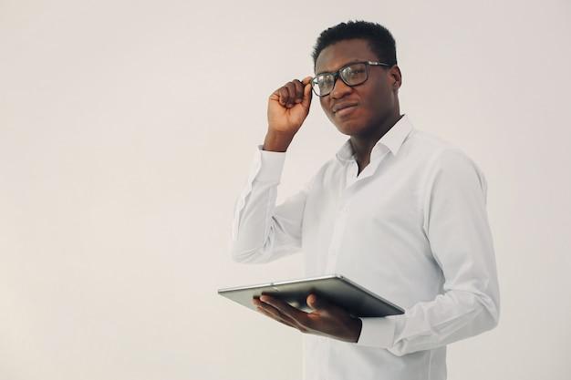 Homem negro bonito, de pé em uma parede branca Foto gratuita