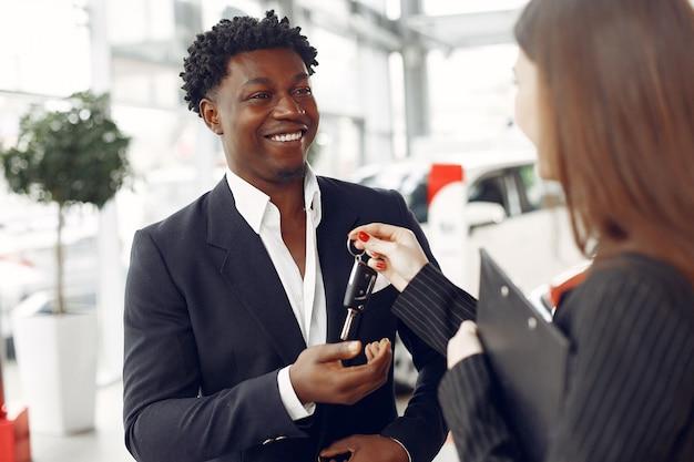 Homem negro bonito e elegante em um salão de carro Foto gratuita