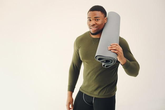 Homem negro bonito fazendo yoga em uma parede branca Foto gratuita