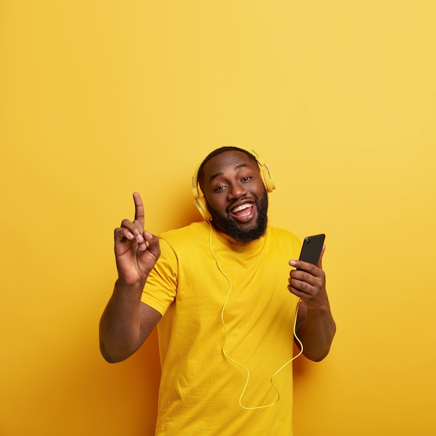 Homem negro com a barba por fazer feliz se arrasta ao ritmo da música, ouve música popular em fones de ouvido, conectado a um smartphone, gosta da lista de reprodução, levanta as mãos, vestido com uma camiseta casual em um tom com a parede Foto gratuita