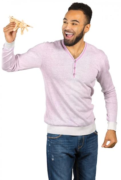 Homem negro com um avião de brinquedo isolado no branco Foto Premium