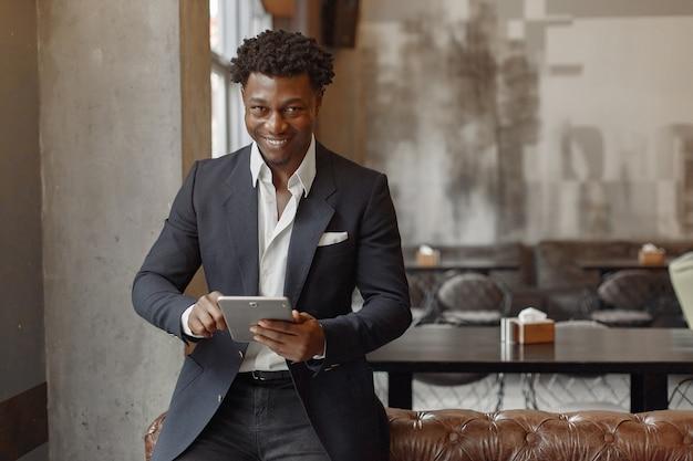 Homem negro em um terno preto em pé em um café Foto gratuita