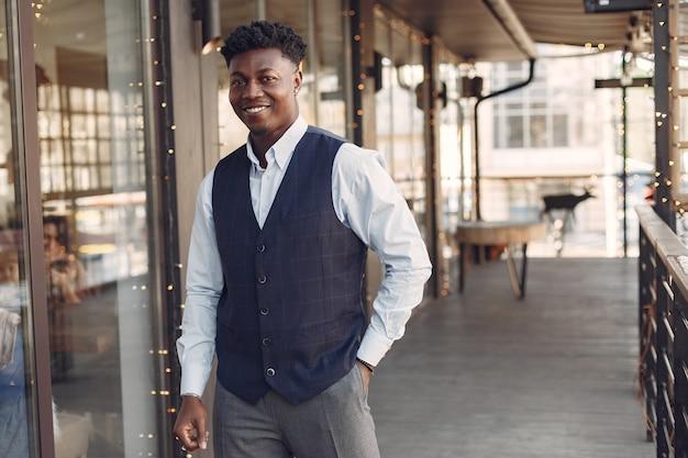Homem negro em uma camisa azul em pé em um café Foto gratuita