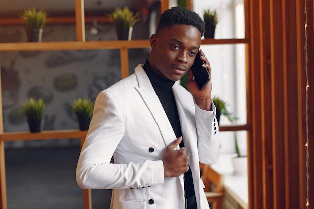 Homem negro em uma jaqueta branca de pé com um telefone Foto gratuita