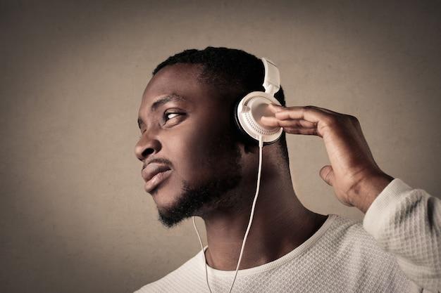 Homem negro, ouvindo música em fones de ouvido Foto Premium