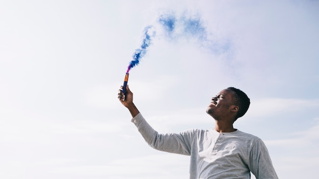 Homem negro segurando bombas de fumaça azuis escuras Foto gratuita