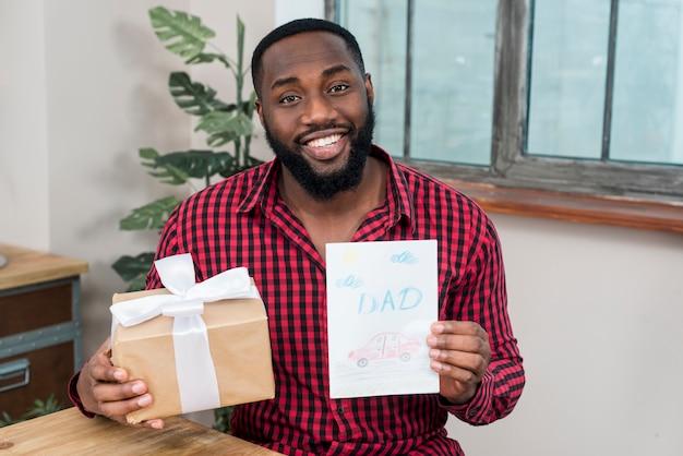 Homem negro, segurando, cartão, e, presente Foto gratuita