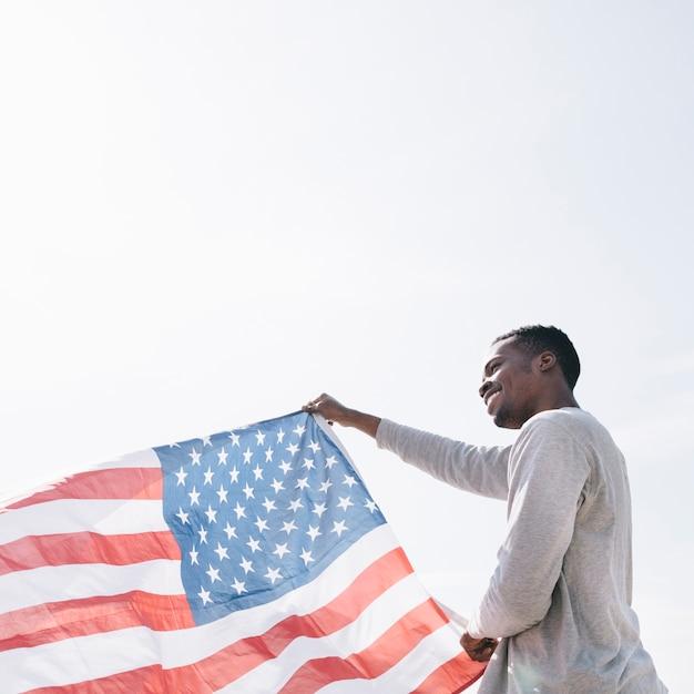 Homem negro sorridente segurando acenando a bandeira americana no sol Foto gratuita