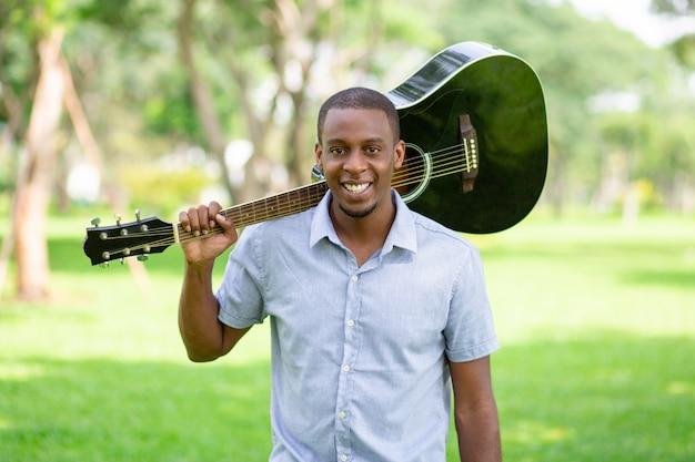 Homem negro sorridente segurando o violão no ombro no parque Foto gratuita