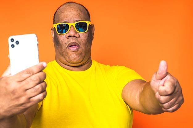 Homem negro usando telefone celular em fundo isolado Foto Premium