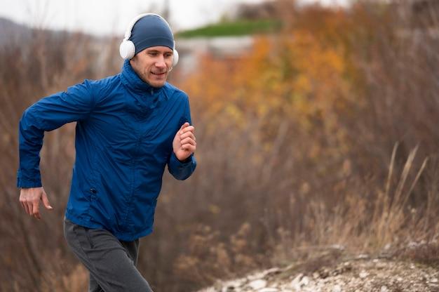 Homem no meio do tiro correndo pela natureza Foto gratuita