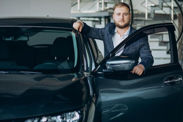 Homem no showroom de carros escolhendo um carro Foto gratuita