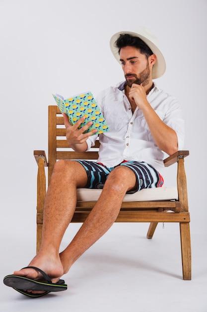 Homem no verão usa leitura de um livro Foto gratuita