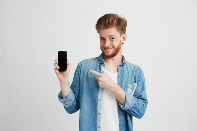 Homem novo bonito alegre que sorri apontando o dedo no smartphone em sua mão sobre o fundo do wite. Foto gratuita