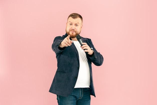 Homem novo com o microfone no rosa, conduzindo com o microfone no conceito do estúdio. Foto gratuita