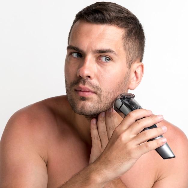 Homem novo considerável que barbeia com o ajustador no contexto branco Foto gratuita