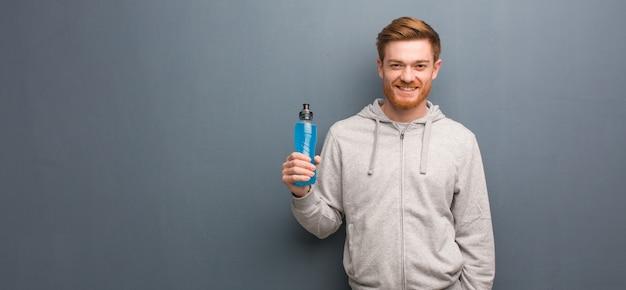 Homem novo da aptidão do ruivo alegre com um sorriso grande. ele está segurando uma bebida energética. Foto Premium