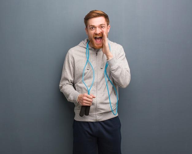 Homem novo da aptidão do ruivo que shouting algo feliz à parte dianteira. ele está segurando uma corda de pular. Foto Premium