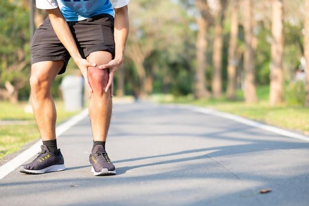 Homem novo da aptidão que guarda seus ferimento de pé dos esportes. músculo doloroso durante o treino Foto Premium