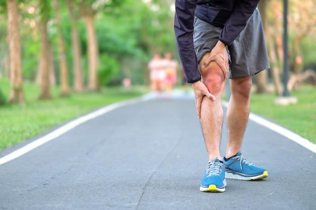 Homem novo da aptidão que guarda seus ferimento de pé dos esportes. Foto Premium