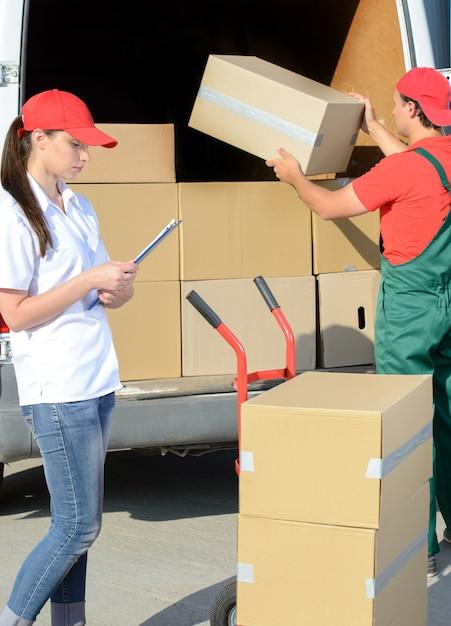 Homem novo de sorriso do correio da entrega postal do homem e da mulher. Foto Premium