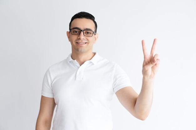 Homem novo de sorriso que mostra o sinal da vitória e que olha a câmera. Foto gratuita