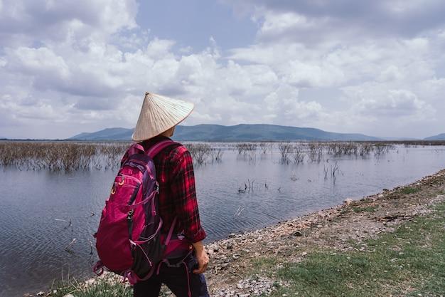 Homem novo do viajante que fica no lago nas horas de verão. Foto Premium