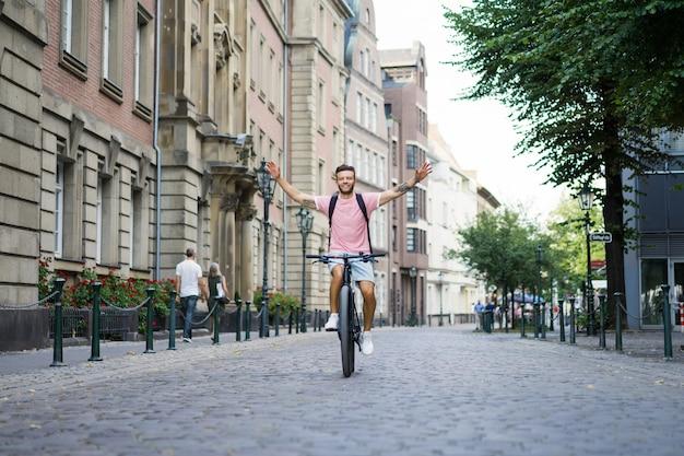 Homem novo dos esportes em uma bicicleta em uma cidade européia. esportes em ambientes urbanos. Foto gratuita