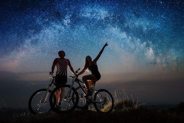 Homem novo e mulher com os mountain bike no monte sob o céu estrelado da noite. Foto Premium