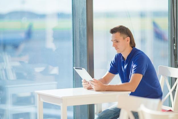 Homem novo em uma sala de estar do aeroporto que espera o avião do voo. Foto Premium