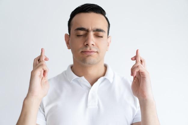 Homem novo focalizado que mantem os dedos cruzados e os olhos fechados. conceito de desejo. Foto gratuita