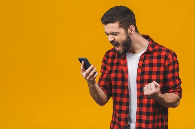 Homem novo irritado que grita no telefone celular isolado em uma parede amarela. Foto Premium