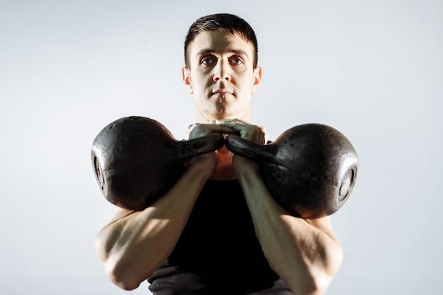 Homem novo muscular que faz o exercício pesado para o bíceps. Foto Premium