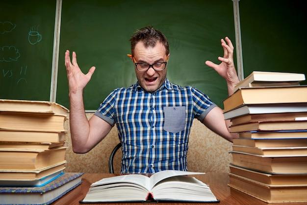 Homem novo não barbeado cansado despenteado louco nos vidros que lê um livro na tabela com as pilhas dos livros na perspectiva do quadro-negro. Foto Premium