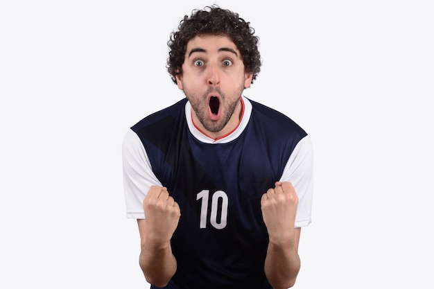 Homem novo no uniforme do futebol do futebol que grita quando sua vitória da equipe. Foto Premium
