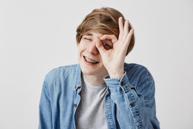 Homem novo positivo com o cabelo louro que fecha os olhos e que sorri com a alegria que mostra o sinal aprovado que está contente após ter encontrado sua namorada isolada contra o fundo cinzento. expressões e emoções do rosto humano Foto gratuita