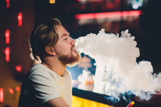 Homem novo que fuma shisha no restaurante árabe - homem que exala a fumaça que inala de um cachimbo de água. Foto Premium