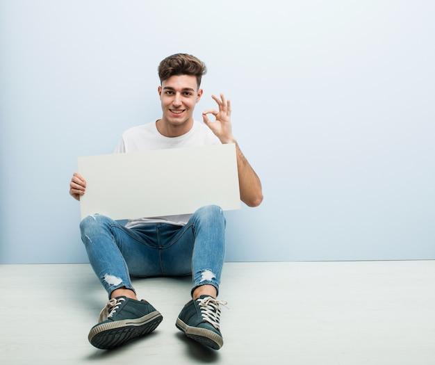 Homem novo que guarda um cartaz que senta-se em seu gesto home da casa alegre e seguro que mostra o aprovado. Foto Premium
