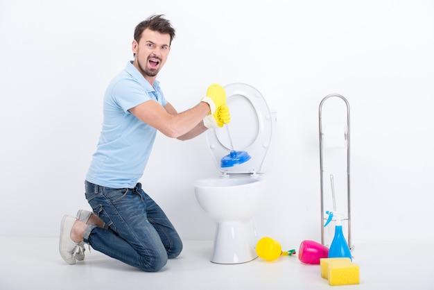 Homem novo que unclogging um toalete com atuador. Foto Premium