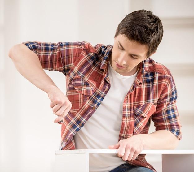 Homem novo que usa ferramentas do reparo para construir a mobília nova. Foto Premium