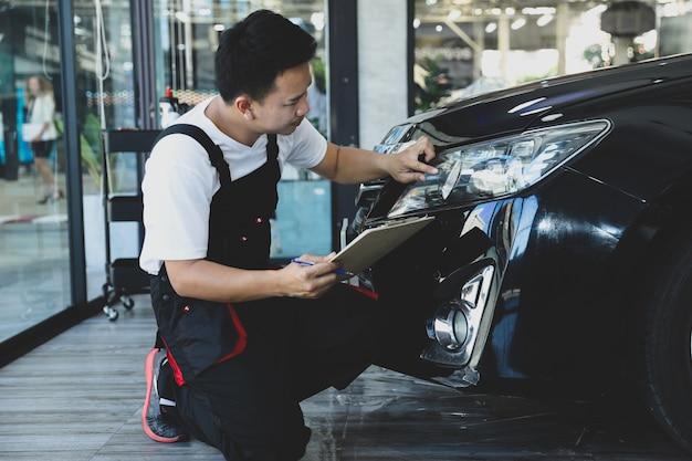 Homem novo que verifica o carro do farol na lista de verificação do caminhão da manutenção preventiva do conceito. Foto Premium