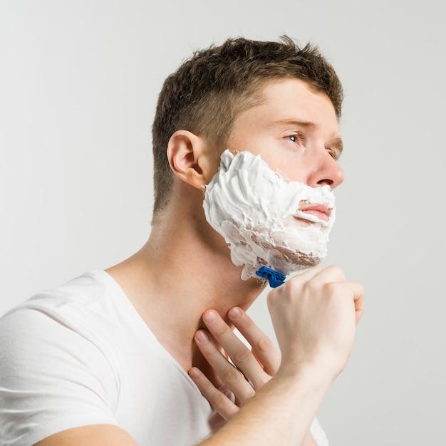 Homem novo sério que barbeia com lâmina azul de encontro ao fundo branco Foto gratuita